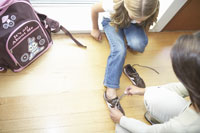 Mother and daughter putting on shoes