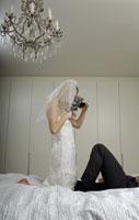 Bride and groom filming on the bed 11029006241| 写真素材・ストックフォト・画像・イラスト素材|アマナイメージズ