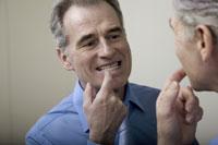 Senior man checking teeth in mirror
