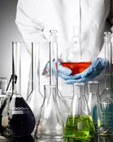 One person holding beaker of liquid