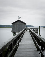 boathouse on lake under overcast sky