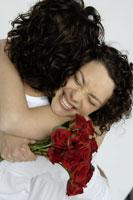 Man hugging Woman with bouquet of roses 11029006699| 写真素材・ストックフォト・画像・イラスト素材|アマナイメージズ
