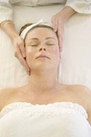 Masseur massaging client's face