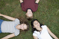 two girls and boy laying in grass