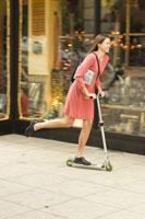 Woman pushing scooter past storefront 11029007268| 写真素材・ストックフォト・画像・イラスト素材|アマナイメージズ