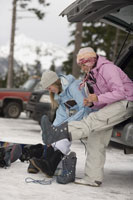 Young women putting on snowboard boots