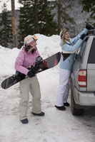 Women unloading snowboard from car  roof