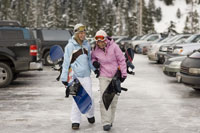 Young women carrying snowboards
