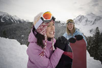Women holding snowboards at top of slope