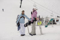 Women holding snowboards by ski lift