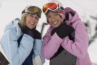 Young women holding snowboards
