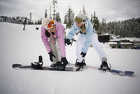 Women strapping boots to snowboards