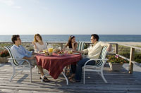Two couples sitting on deck near beach