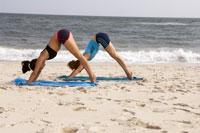 Two women practicing yoga on beach