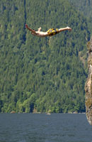 Man cliff diving into lake