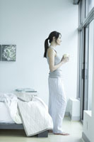 Young adult woman standing in bedroom