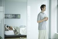 Man drinking coffee in bedroom