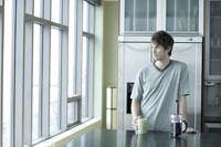 Man drinking coffee in kitchen