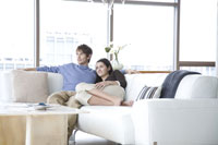 Young adult couple sitting on sofa
