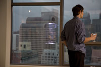 Young adult man looking out window