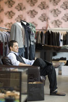 Man sitting in chair in clothing store