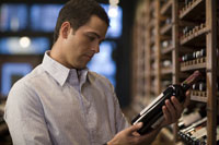 Man looking at wine in liquor store