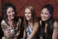 Three young women sitting at nightclub