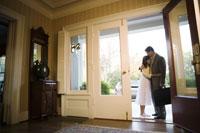 man kissing his daughter in open door
