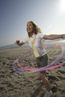 Woman with hula hoops on the beach
