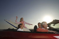 Couples  in convertible with surfboard