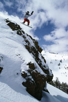 Snowboarder jumping off rock face