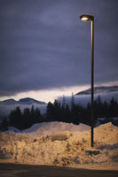 Street light in snow bank by parking lot