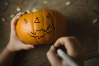 Child drawing face on pumpkin with a pen