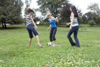 Three girls playing with soccer ball