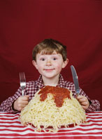 Young boy with giant plate of spaghetti
