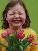 Young girl wrinkling her nose at tulips