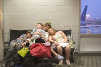 Family asleep in waiting area of airport