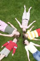 Children laying on grass 11029008836| 写真素材・ストックフォト・画像・イラスト素材|アマナイメージズ
