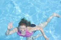 Girl waving underwater in swimming pool 11029008858| 写真素材・ストックフォト・画像・イラスト素材|アマナイメージズ