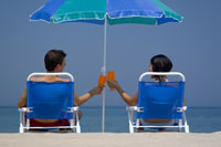 Couple toasting in lawn chairs on beach
