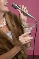 Mature woman singing and holding martini 11029008993| 写真素材・ストックフォト・画像・イラスト素材|アマナイメージズ