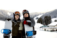 Boys holding snowboards on slopes
