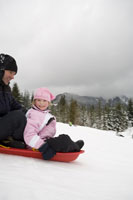 Father and daughter sledding in snow