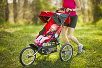 Woman jogging with baby in a stroller