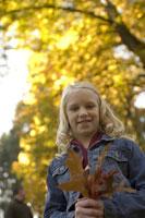 Young girl holding autumn leaf 11029009420  写真素材・ストックフォト・画像・イラスト素材 アマナイメージズ