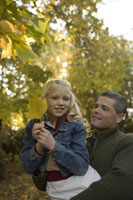 Father holding daughter holding leaf
