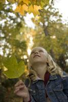 Young girl holding autumn leaf 11029009423  写真素材・ストックフォト・画像・イラスト素材 アマナイメージズ