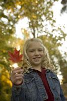 Young girl holding autumn leaf 11029009424  写真素材・ストックフォト・画像・イラスト素材 アマナイメージズ