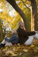 Mother and daughter sitting in leaves