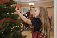 Youn girl decorating Christmas tree